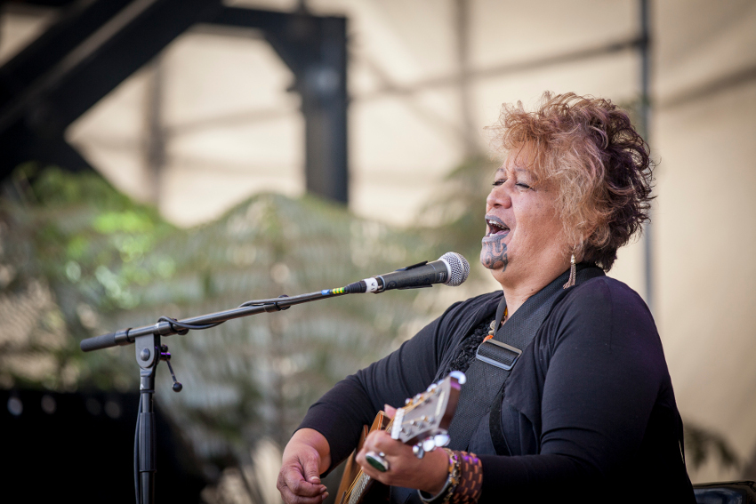 A Māori performer singing and playing the guitar.