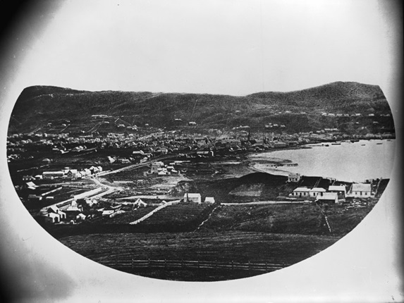 A historical photograph of Wellington harbour, with small settlements around the shoreline.