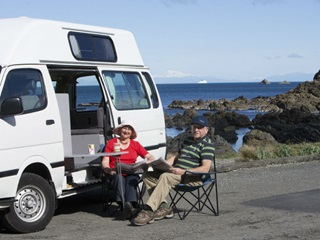 Two people sitting at a table by their campervan on Wellington's south coast.