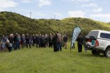 A group of people in a green field attending the opening celebrations for the Te Ara Paparārangi track.