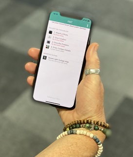 Image of hand holding phone with FixIt app on screen