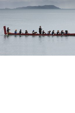 An ornate waka with 12 paddlers in the Wellington harbour.
