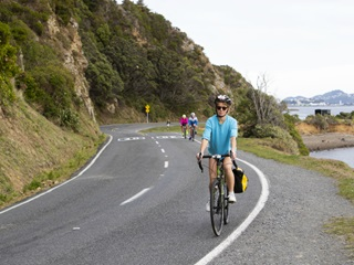 A person cycling along a coastal road with other cyclists following in the background.