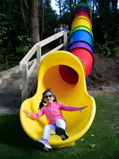 Child sliding out of a long rainbow tube slide.