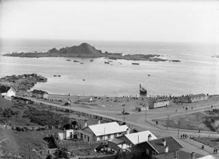 Historic photo of the beach at Island Bay and showing Tapiteranga Island. Taken by Sydney Charles Smith 1888-1972.