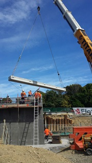 A crane lifts a beam into position on the new Broderick Road bridge.