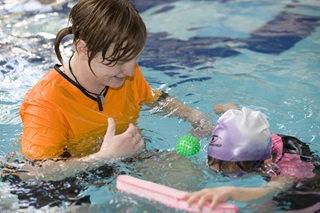 Instructor and preschooler in learn to swim lesson.