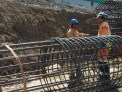 Workers next to a cage of reinforcing steel.